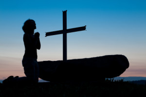 Woman praying at cross