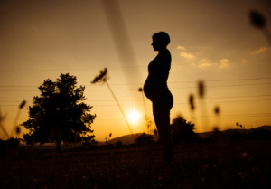 Silhouette of pregnant woman in the sunset