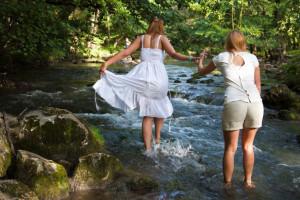 2 girls crossing stream together